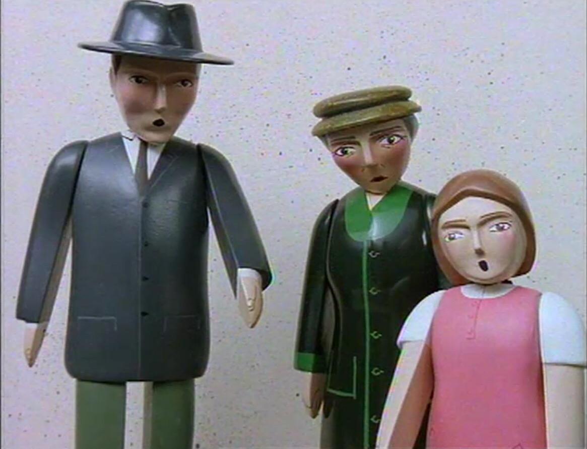 キンドリー夫人とブリジット・ハットと共にいる薄黒いスーツの男性
